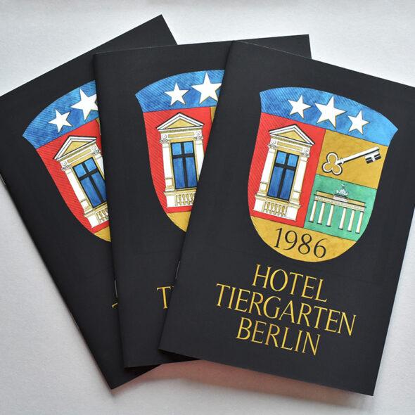 Wappen vom Hotel Tiergarten als Logo (drei Sterne, Fenster, Schlüßel, Brandenburger Tor, Gründungsjahr 1986) auf Gästemappen
